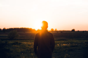 Foto einer Person von hinten, die einen Sonnenaufgang betrachtet // by Warren Wong on Unsplash