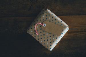 Foto eines kleinen in Papier eingewickelten Geschenks auf Holzunterlage