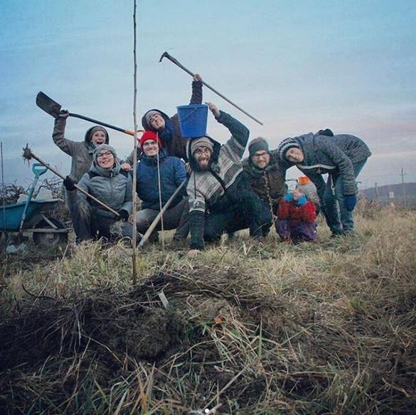ein Gruppe von Menschen, die mit Gartenwerkzeugen posiert