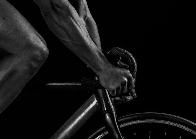 Foto eines Rennrads. Ausschnitt. Nur Arme und Beine der Person auf dem Fahrrad sichtbar.