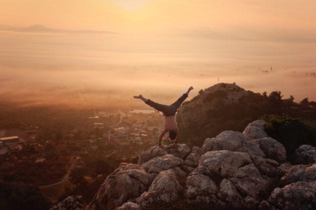 Foto einer Person im Handstand auf einem Berg