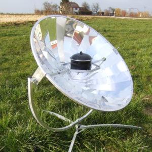 Foto eines Solarkochers mit Topf auf einer grünen Wiese