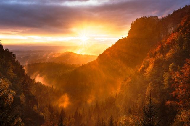 Foto einer rötlichen Sonne in den Bergen