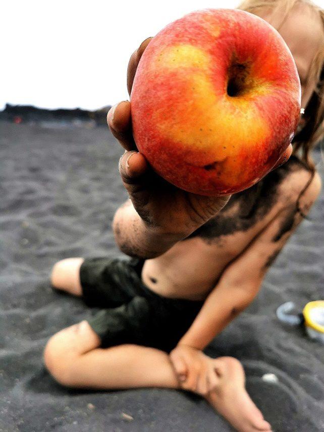 Kind reicht Apfel in die Kamera
