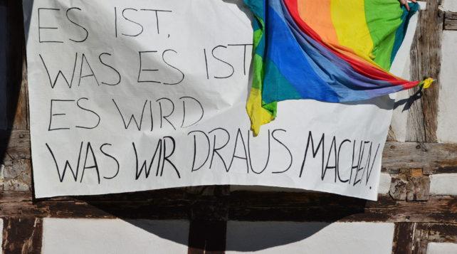 Banner an einer Hauswand mit dem Spruch: Es ist was es ist. Es wird, was wir draus machen. --- Dem Slogan von AnsteckendSolidarisch