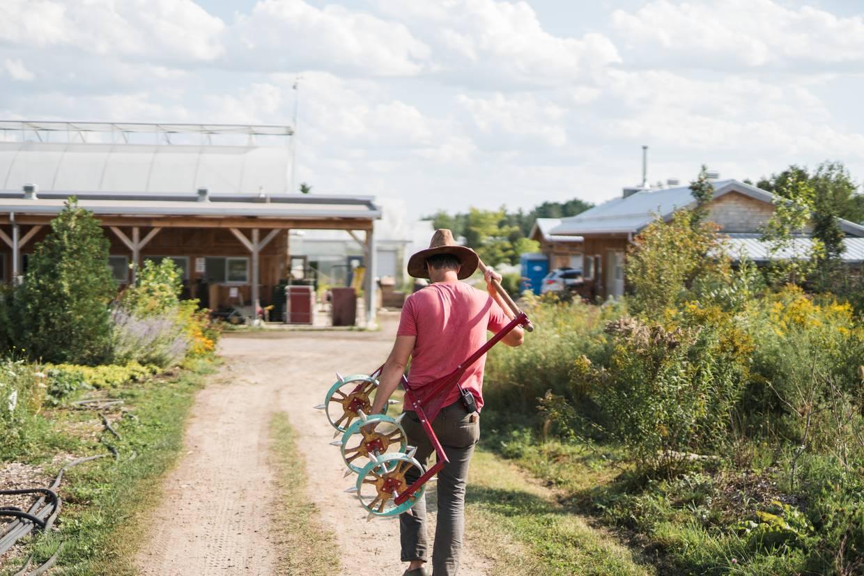 Der Autor und Landwirt Jean Martin Fortier mit einer Maschine auf dem Weg durch seinen kleinskalierten Betrieb