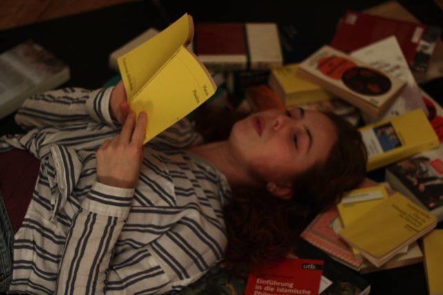 Foto einer Studierenden, die auf vielen Büchern liegt und ein Buch liest.
