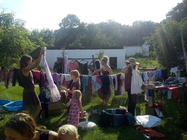Mitglieder der Foodcoop, die im sonnigen Garten Secondhand-Kleidung anprobieren und tauschen