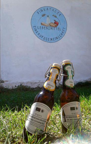 Bierflaschen in der Wiese vor dem Foodcoop-Lager, dahinter das Logo der Pinkataler Lebensmittel Einkaufsgemeinschaft an die Wand gemalt
