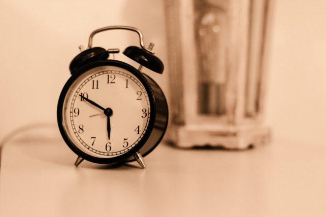 Ein schwarzer Wecker, der eine Zeit anzeigt, auf einem hellen Hintergrund. In der Früh schon aktiv werden ist eine Entscheidung!