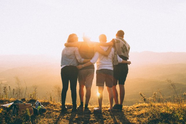 Vier Menschen stehen nebeneinander auf einem Berg, die Arme umeinandergelegt und schauen in den Sonnenaufgang