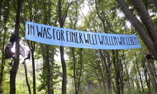 Aktionsbanner, der Gutes Leben für alle fordert. Schriftzug am Banner, der zwischen zwei Bäumen gespannt ist lautet: In was für einer Welt wollen wir leben?